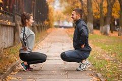 做在彼此对面的夫妇仰卧起坐 在秋天公园 库存图片
