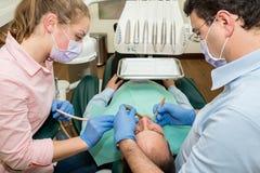做在患者的牙医一种牙齿治疗 免版税库存图片