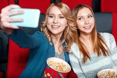 做在戏院的两个俏丽的女孩selsie 免版税库存图片