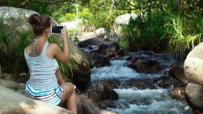 做在手机的美丽的妇女照片,当旅行在密林森林妇女游人时的山瀑布 股票视频