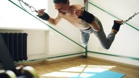 做在扎营的年轻人瑜伽设备的exircise和跟他开玩笑胳膊和有绳索的 图库摄影