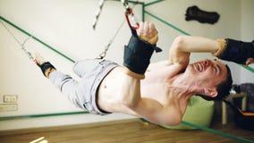 做在扎营的年轻人瑜伽设备的exircise和跟他开玩笑胳膊和有绳索的 免版税图库摄影