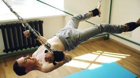 做在扎营的年轻人瑜伽设备的exircise和跟他开玩笑胳膊和有绳索的 库存照片
