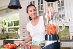 做在搅拌器的可爱的妇女圆滑的人在现代厨房里 免版税库存图片