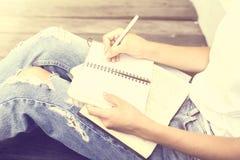做在日志的女孩笔记 免版税库存图片