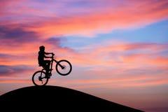 做在日落天空的Mountainbiker自行车前轮离地平衡特技在小山 库存照片