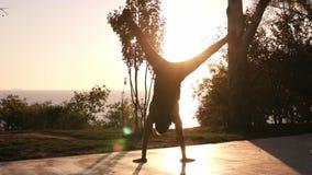 做在日落或日出之外的年轻人手倒立 健身男性运动员锻炼 体育室外生活方式锻炼 股票视频