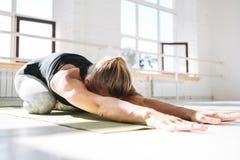 做在晴朗的胶的运动的坚强的妇女实践的瑜伽健身席子 免版税库存图片