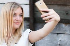 做在智能手机的女孩selfie 库存图片