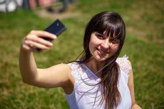 做在智能手机的美丽的东方女孩selfie 免版税库存照片