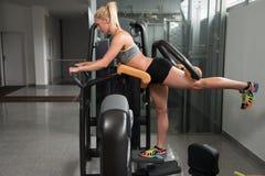 做在机器的健康少妇腿部锻炼 免版税库存照片