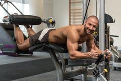 做在机器的爱好健美者说谎的腿卷毛锻炼 免版税库存照片
