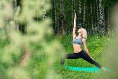 做在桦树树树丛视图的女孩瑜伽 免版税库存图片