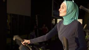 做在模拟器的hijab的年轻运动的回教妇女体育在窗口前面 关闭 影视素材
