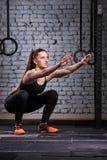做在残酷内部的肌肉美丽的妇女蹲坐 Crossfit 免版税库存图片