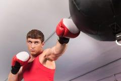做在沙袋的拳击手一些训练在健身房 库存照片