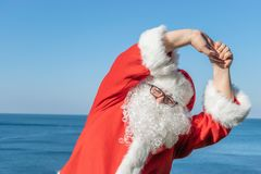 做在海洋的圣诞老人锻炼 传统红色成套装备和放松在海滩 库存照片