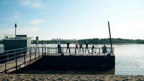 做在海滩的人们、男人和妇女锻炼在好天气 小组女孩和男孩训练 健身小组 股票录像