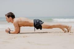 做在海滩的健身人俯卧撑锻炼 制定出他的与pushup锻炼o的适合人画象胳膊肌肉和身体核心 库存照片