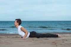 做在海滩的女孩瑜伽姿势 免版税库存图片