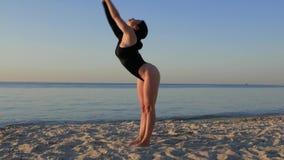 做在海滩的黑紧身衣裤的运动的妇女瑜伽靠近海在令人惊讶的日出 健身、体育、瑜伽和健康生活方式 影视素材