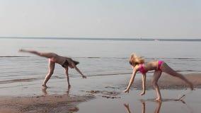 做在海滩的两个女孩杂技 股票视频