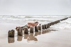 做在海滩的人俯卧撑 库存图片