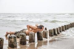 做在海滩的人俯卧撑 免版税库存照片