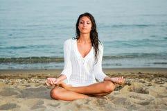 做在海滩的俏丽的妇女瑜伽 免版税库存图片