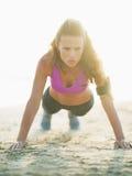 做在海滩的健康少妇俯卧撑 免版税库存照片