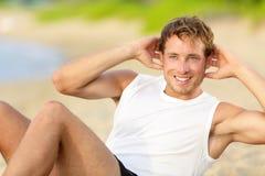 做在海滩的健身人咬嚼仰卧起坐 免版税库存图片