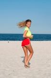 做在海滩的健身妇女锻炼 库存图片
