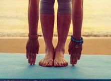 做在海滩的女孩瑜伽锻炼 免版税库存图片