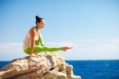 做在海滩的女孩瑜伽 库存图片