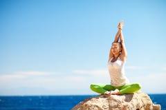 做在海滩的女孩瑜伽 库存照片
