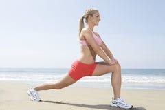 做在海滩的妇女健身锻炼 库存图片