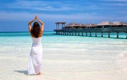 做在海滩的妇女瑜伽 库存图片