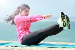 做在海滩的妇女锻炼 库存图片
