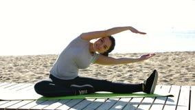 做在海滩的微笑的女孩锻炼在晴朗的早晨 股票录像