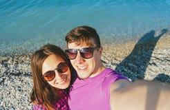 做在海滩的愉快的爱恋的夫妇自画象 免版税图库摄影
