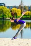 做在海滩的蓝色运动衫的年轻浅黑肤色的男人一个跃迁 做健身锻炼的妇女户外 库存照片