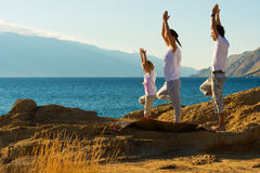 做在海滩的年轻家庭瑜伽锻炼 免版税库存图片