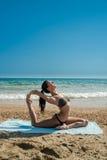 做在海滩o的一名美丽的妇女的照片瑜伽锻炼 免版税库存图片