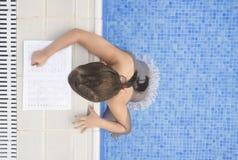 做在游泳游泳池边的儿童女孩假日家庭作业 免版税图库摄影