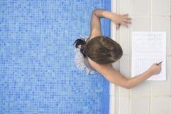 做在游泳游泳池边的儿童女孩假日家庭作业 库存照片