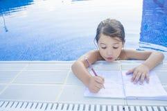 做在游泳游泳池边的儿童女孩假日家庭作业 免版税库存照片