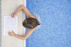 做在游泳游泳池边的儿童女孩假日家庭作业 免版税库存图片