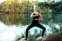 做在湖的一件黑T恤杉和绑腿的少女瑜伽在公园 免版税库存照片