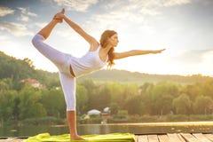 做在湖的妇女瑜伽-美好的光 库存照片