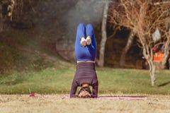 做在湖的岸的妇女瑜伽 免版税库存图片